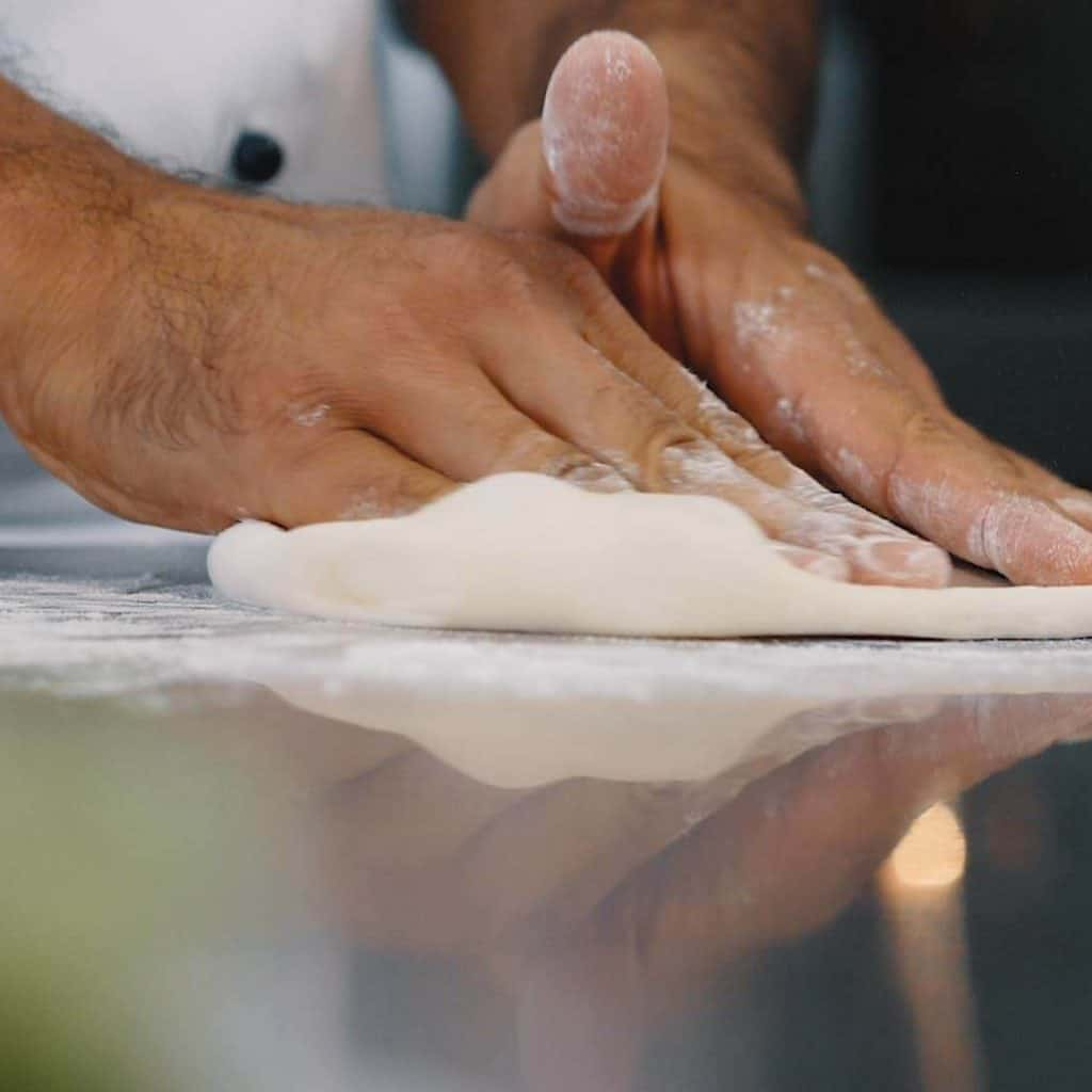 Zwei mehlige Hände kneten Pizzateig, Koch bei Vorbereitung für Pizzabacken, Rational AG, Foto Social Media Content, WINGMEN Media