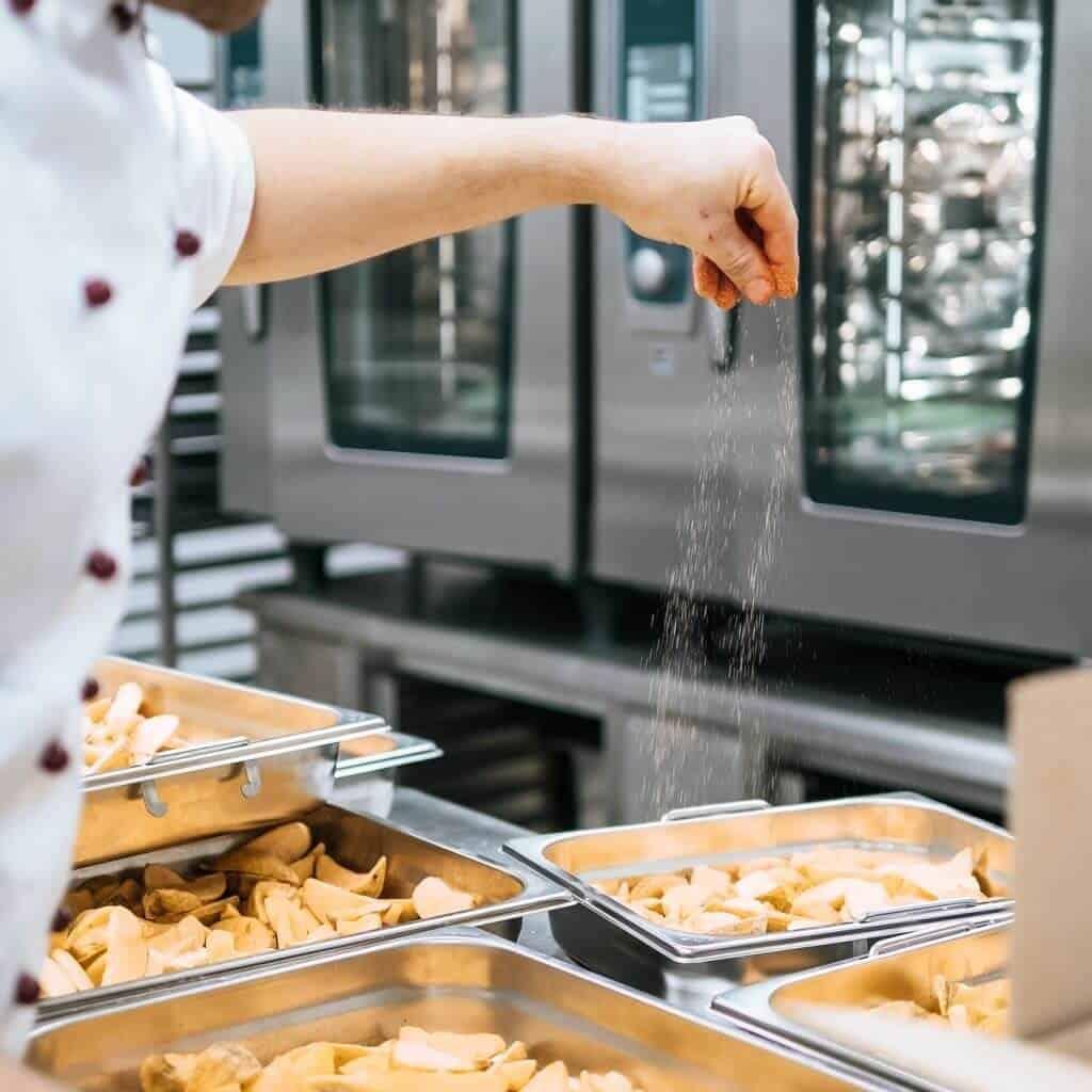 Ein Koch streut Salz auf Kartoffelecken, Rational Geräte im Hintergrund, Rational-Konzept in der modernen Großküche, Rational AG, Foto Social Media Content, WINGMEN Media