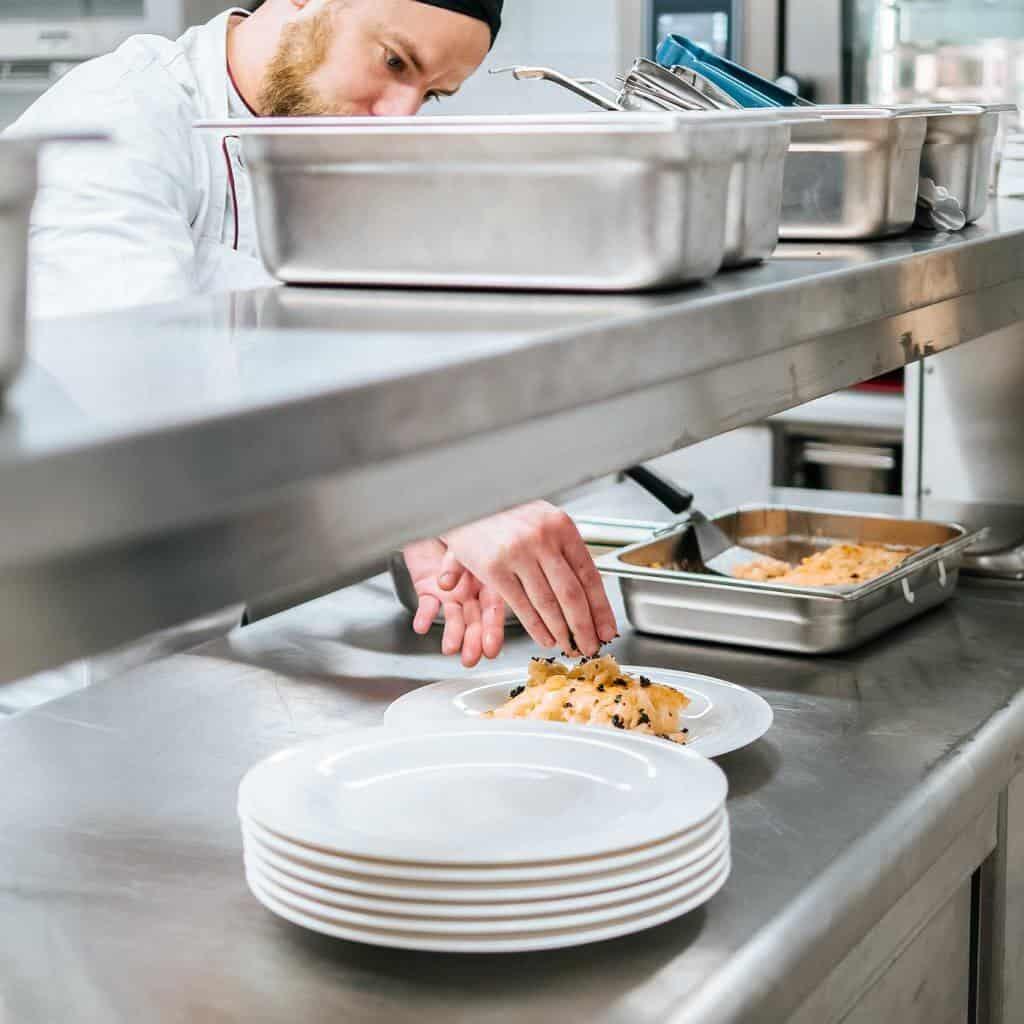 Ein Koch serviert fertiges Gericht auf Teller, Finishing, Rational-Konzept in der modernen Großküche, Rational AG, Foto Social Media Content, WINGMEN Media