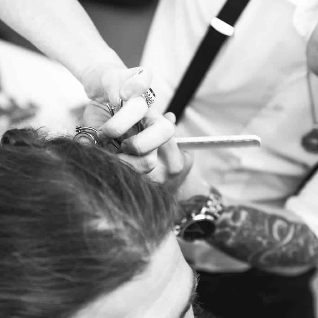 Barber bei der Arbeit mit Kunden, Vollbart, Barber schneidet mit Schere, Vintage Look, Schwarzweiß Aufnahme, steinzeit für haare, Recruitingfilm, WINGMEN Media