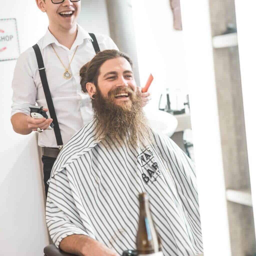 Ein lachender, glücklicher Kunde im Barber Shop, hinter ihm steht Barber mit Kamm und Rasier, steinzeit für haare, Recruitingfilm, WINGMEN Media