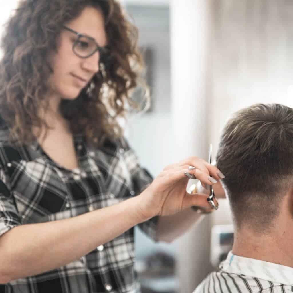 Im Barber Shop werden die Haare eines Kunden geschnitten, Handwerk, eine junge Frau schneidet Haare, Team Barber, steinzeit für haare, Recruitingfilm, WINGMEN Media