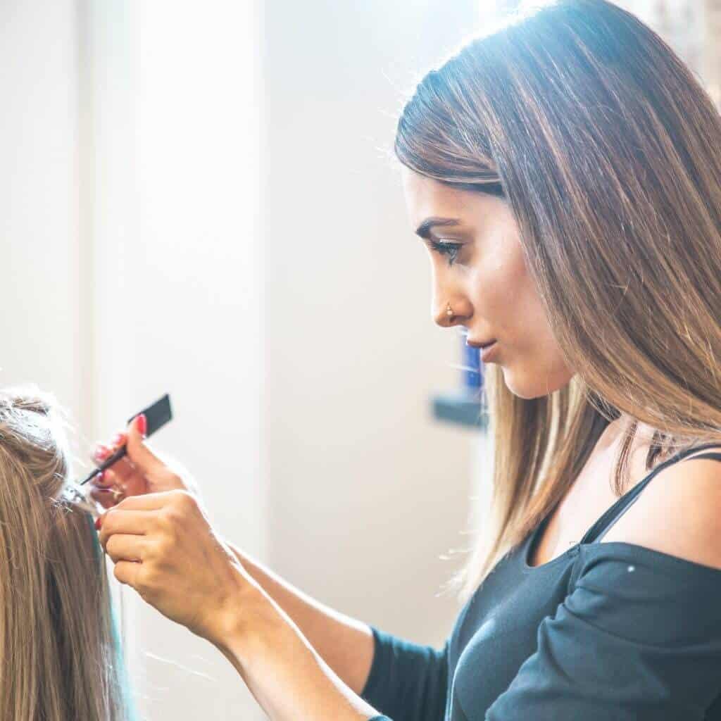 Eine Friseurin arbeitet mit Kamm bunte Strähnen ins Haar einer Kundin ein, Steinzeit Barber Shop, steinzeit für haare, Recruitingfilm, WINGMEN Media