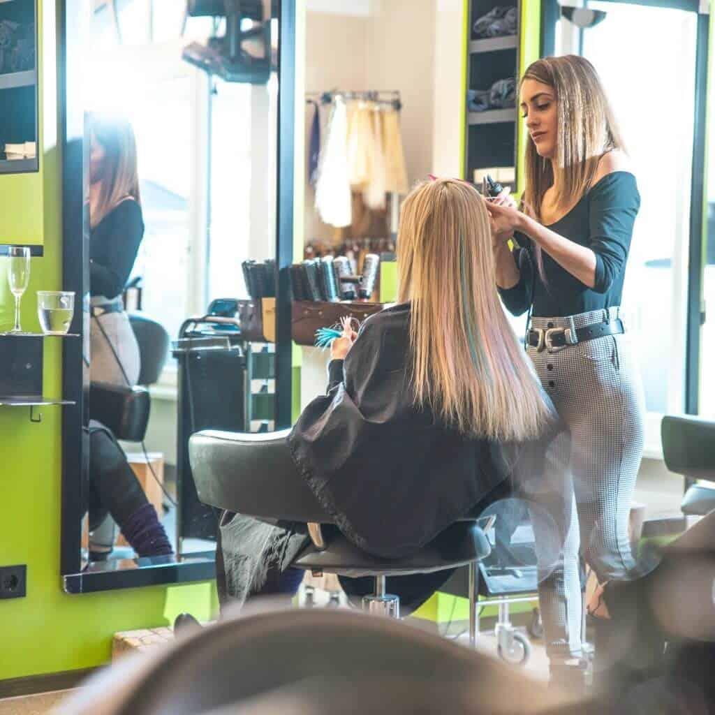 Eine Friseurin arbeitet bei Kundin bunte Strähnen ins Haar ein, Damen- und Herren Friseur in Prien am Chiemsee, steinzeit für haare, Recruitingfilm, WINGMEN Media