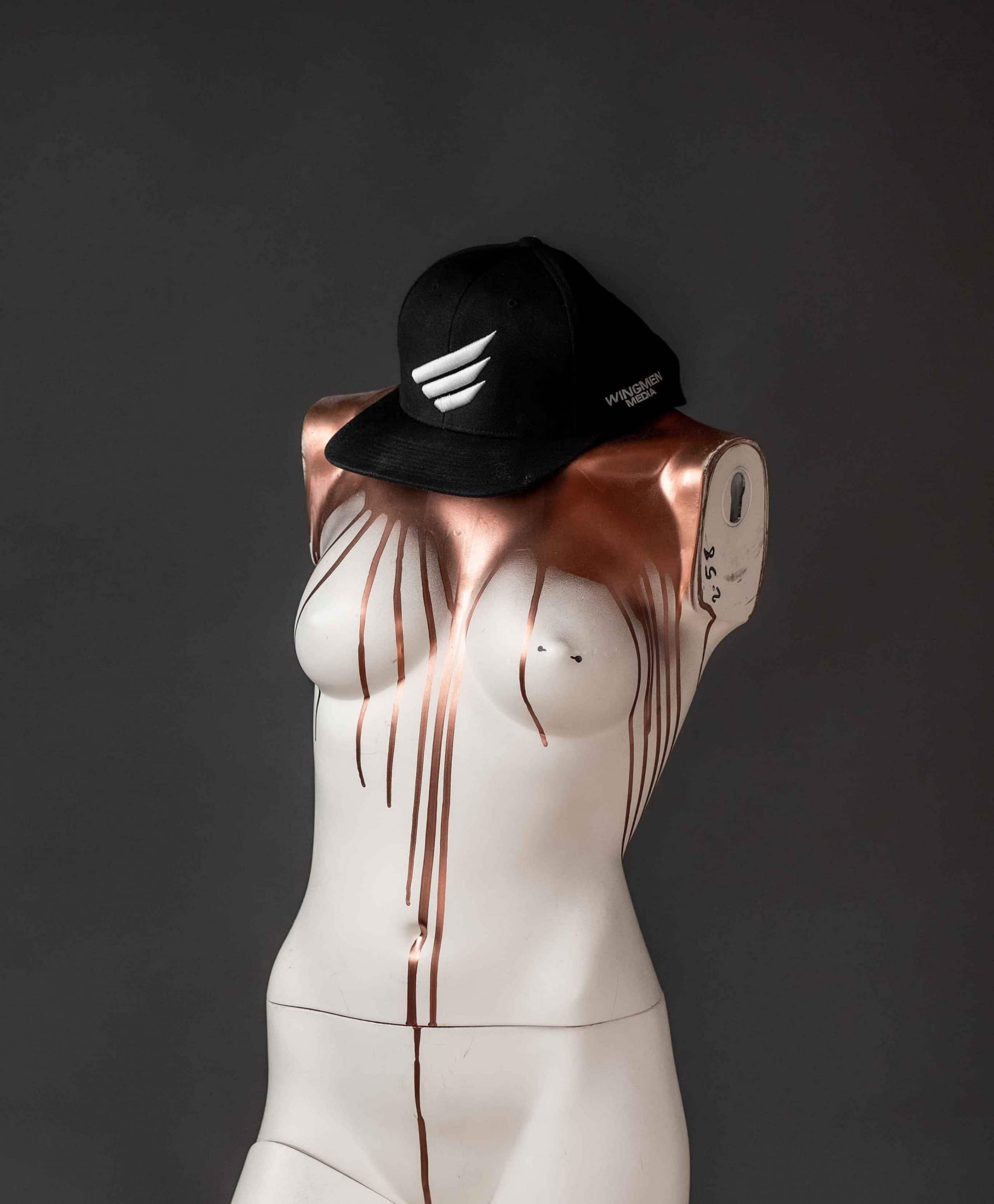 Eine Schaufensterpuppe ohne Arme und Kopf, mit Bronze, Metaleffect Farbe überlaufen, trägt ein WINGMEN Media Cap, Logo, Schrift, Unternehmensfotografie, WINGMEN Media