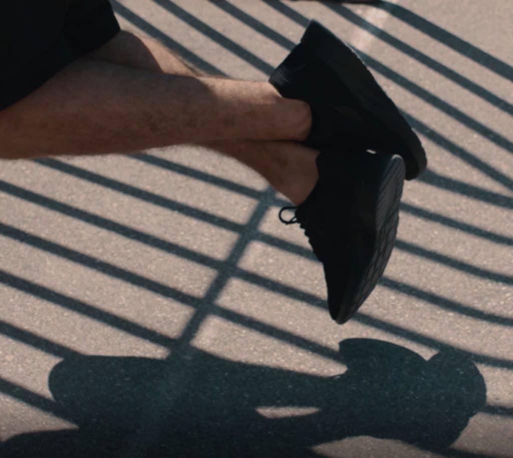 Zwei übereinander geschlagene Füße während einem Klimmzug, Schatten von Fußballtor auf dem Boden, Workout, Sneaker, digitale Coach, Freeletics, Trailer, Social Media Kampagne, WINGMEN Media