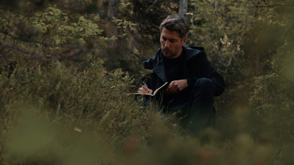 Ein Mann sitzt im Wald, Natur, Grünen, und zeichnet in einem Notizbuch, Skizze, Lebensräume, nordweis Unternehmensgruppe, Imagefilm, Moodfilm, WINGMEN Media