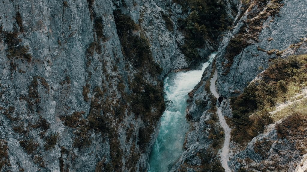 Ein Fluss zwischen Bergen und ein Weg auf dem eine Person geht, Natur, Lebensräume, nordweis Unternehmensgruppe, Imagefilm, Luftaufnahme, WINGMEN Media