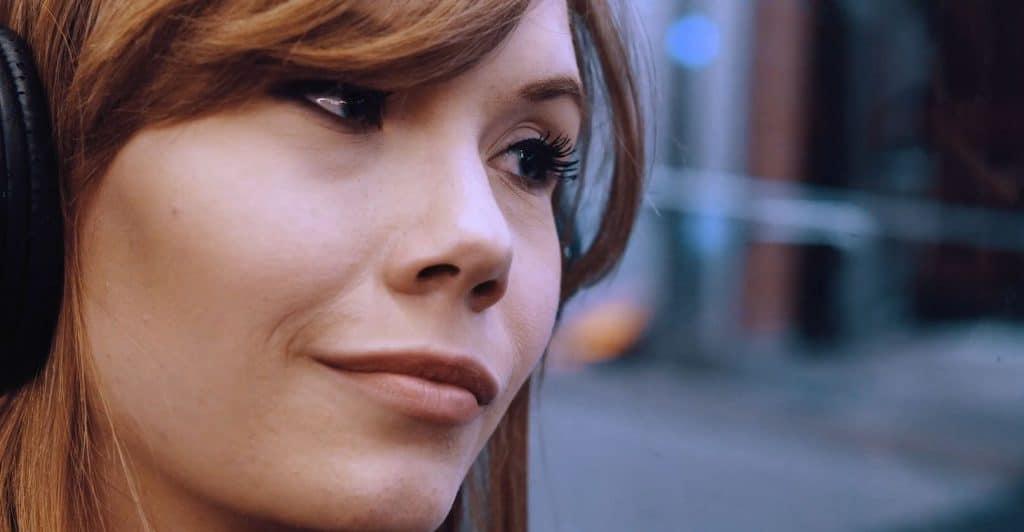 Close Up einer jungen Frau, die ihr Gesicht an Fensterscheibe in der U-Bahn lehnt und raussieht, Kopfhörer, weibliche hero Figur, IT-SA - Die IT-Security Messe und Kongress, Werbespot, pre-roll-ad, Event teaser, WINGMEN Media
