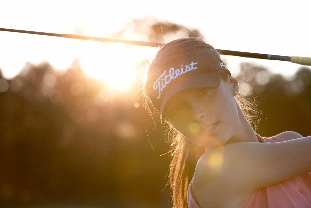 Eine Golfspielerin holt mit Golfschläger für Schuss aus, Golf, Lens Flare, professionelle Ballspeed-Messung, Ballspeedometer, Lifestylefotografie, WINGMEN Media