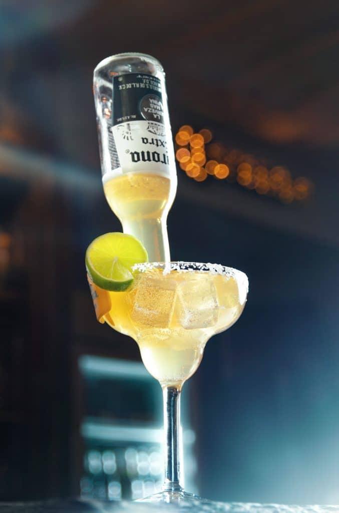 Ein Cocktail mit Eiswürfeln, Limette und Zuckerrand und eine Flasche steckt im Glas, Tiefenschärfe, Bokeh, Getränk, Cocktailbar, Aschau, Chalet Cocktailbar, Produktfotografie, Food Fotografie, WINGMEN Media