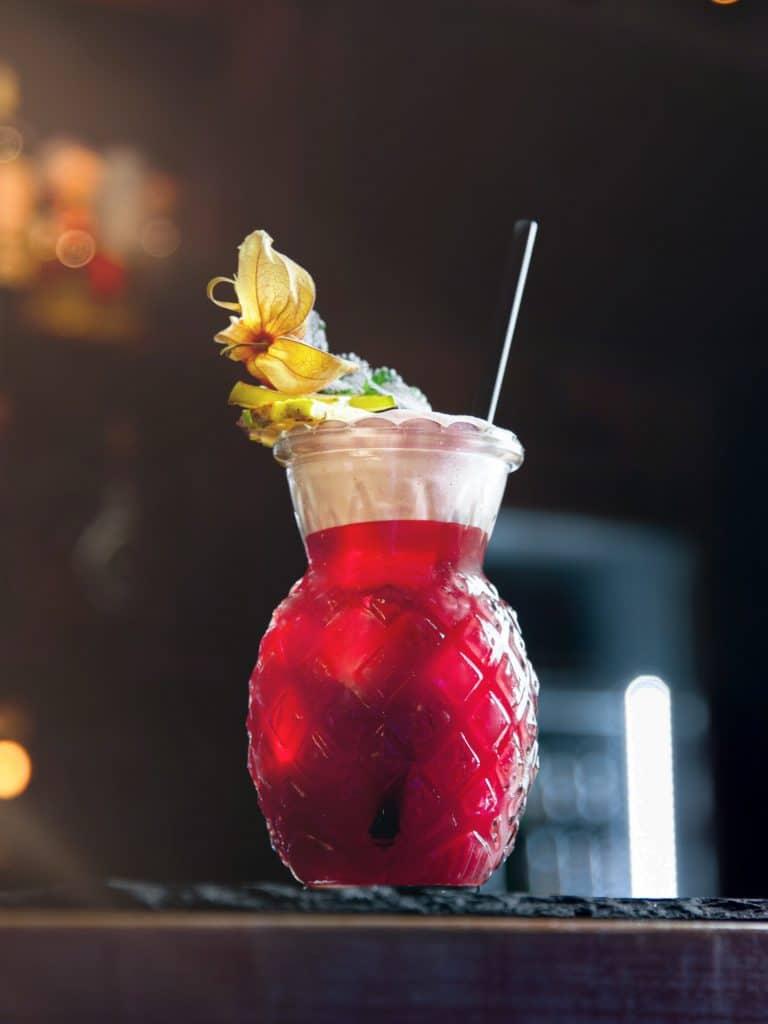 Ein dunkelroter Cocktail in einem Glas mit Ananas Form, dekorierter Cocktail, Tiefenschärfe, Bokeh, Bartheke, Chalet Cocktailbar, Produktfotografie, Food Fotografie, WINGMEN Media
