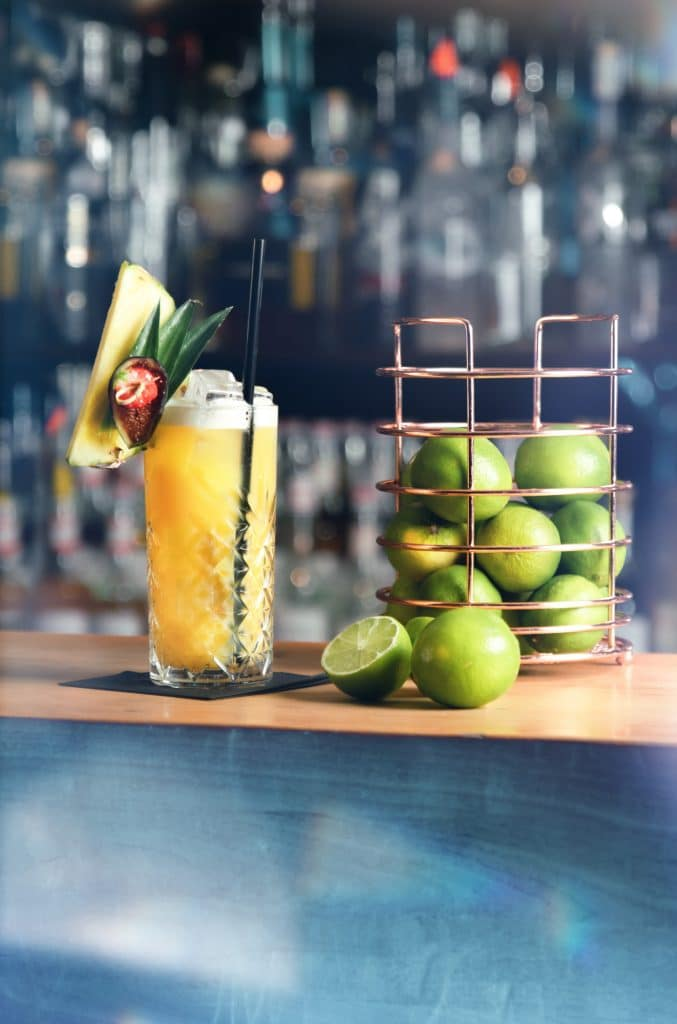 Ein leckerer, tropischer, schön dekorierter Cocktail steht neben einem Limetten Behälter auf der Theke einer Bar, Tiefenschärfe, Bar im Hintergrund, zwischen München und Salzburg, Chalet Cocktailbar, Produktfotografie, Food Fotografie, WINGMEN Media