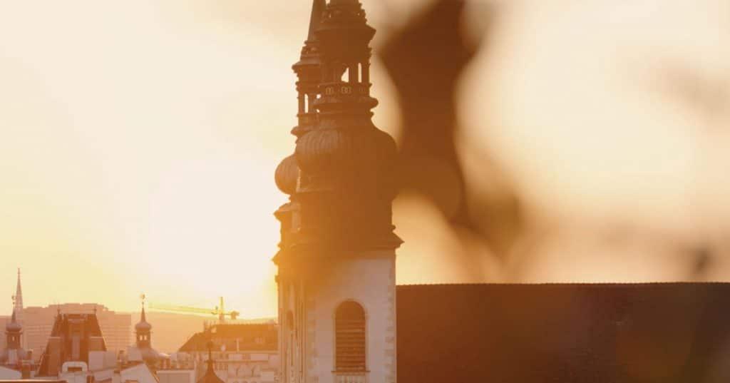 zwei Kirchtürme, Hochhäuser im Hintergrund bei Sonnenuntergang, Wien, MG Real Estate GmbH, Immobilienfotografie, Imagefilm, WINGMEN Media