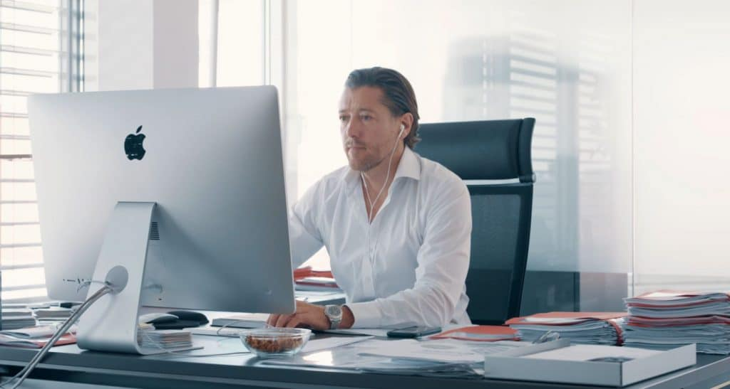 Ein Mann in einem weißen Hemd sitzt an Büroarbeitsplatz am Apple iMac, Arbeit, Büro, clean, Gewerbeimmobilien in Österreich und der gesamten CEE-Region, MG Real Estate GmbH, Unternehmensfotografie, Imagefilm, WINGMEN Media