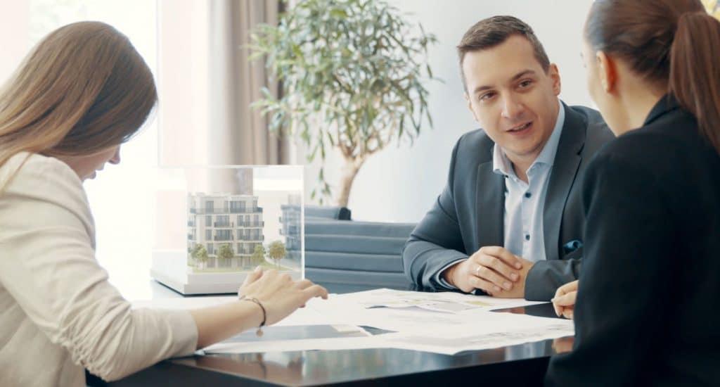Drei Personen sitzt an einem Konferenztisch und besprechen Pläne, ein Immobilienmodell steht auf dem Tisch, nationale und internationale Immobilienberatung, MG Real Estate GmbH, Unternehmensfotografie, Imagefilm, WINGMEN Media