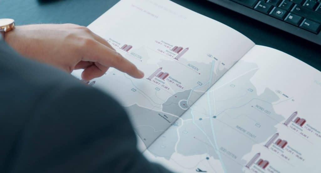 Over the Shoulder Shot von einer Hand, die auf eine Karte mit Immobilien Markierungen zeigt, internationale und nationale Immobilienberatung, MG Real Estate GmbH, Immobilienfotografie, Imagefilm, WINGMEN Media