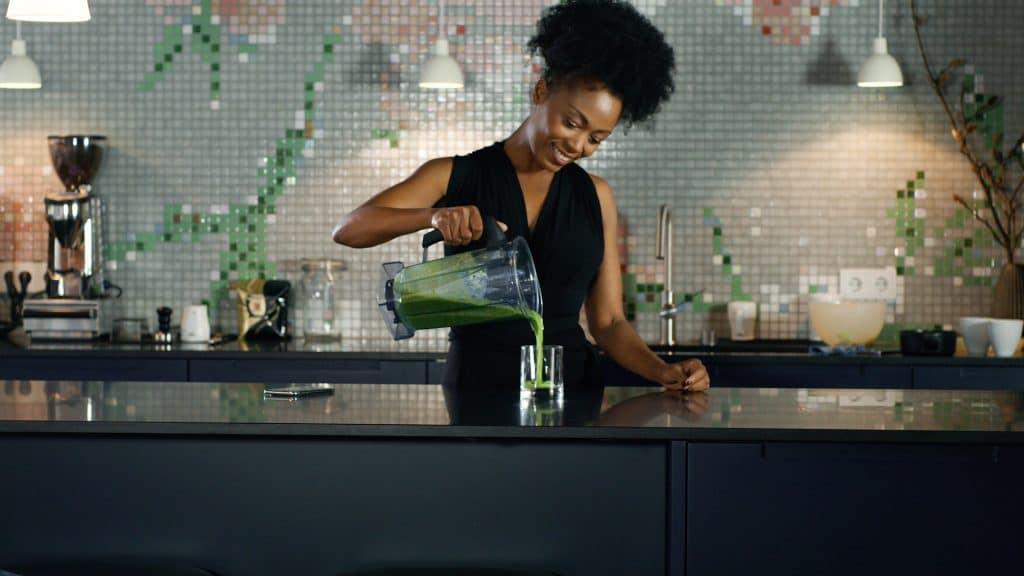 Eine lachende Frau schenkt sich einen frischen Smoothie in ein Glas ein, sie steht in der Küche, gesunde Ernährung, My Blossom, Imagefilm, Erklärfilm, Teaser, WINGMEN Media
