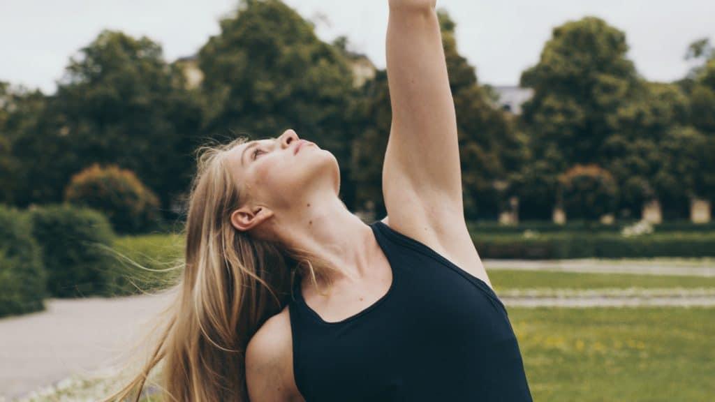 Eine junge Frau in Sportklamotten macht Yoga in einem Park, ihr Arm ist nach oben gestreckt, Mindfulness, App, My Blossom, Imagefilm, Erklärfilm, Teaser, WINGMEN Media