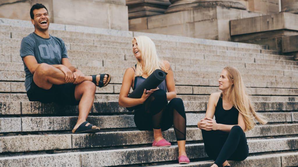 Zwei Frauen und ein Mann sitzen draußen auf Treppenstufen und lachen, sie tragen Sportklamotten, Sportmatte, Yoga, Pilates, My Blossom, Imagefilm, Erklärfilm, Teaser, WINGMEN Media
