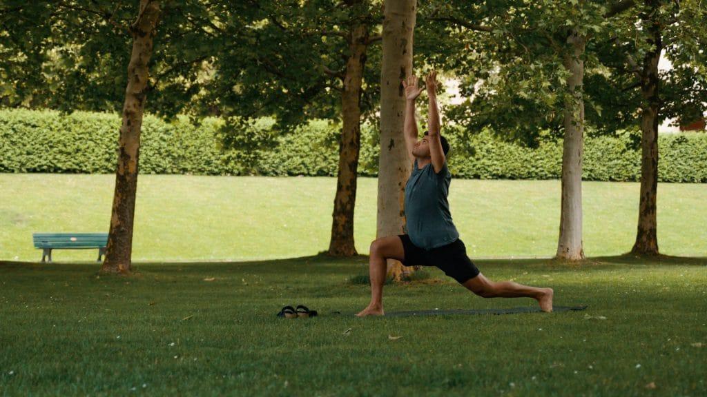 Ein Mann in kurzen Sportklamotten macht in einem Park Yoga Übungen mit der My Blossom App, Natur, Sport, Mindfulness, My Blossom, Imagefilm, Erklärfilm, Teaser, WINGMEN Media
