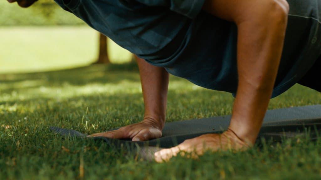 Auf einer Sportmatte in einer Wiese stützen zwei Hände von einem Mann während einer Pilates, Yoga Übung, Sommer, App, My Blossom, Imagefilm, Erklärfilm, Teaser, WINGMEN Media