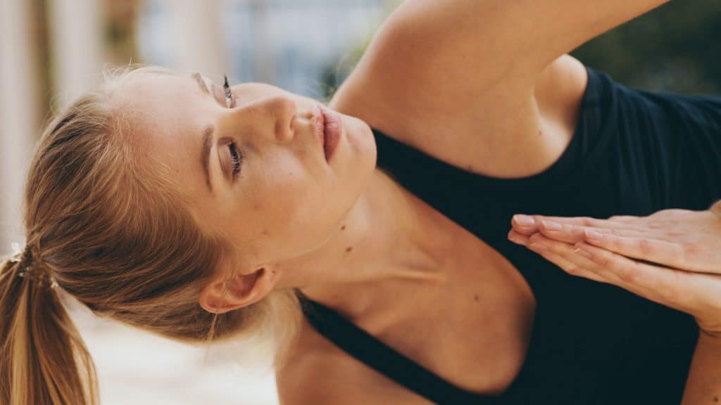 Eine junge Frau mit blonden Haaren und schwarzem Sporttop blickt Richtung Himmel während Yoga Übung, Pilates, Mindfulness, self care, My Blossom, Imagefilm, Erklärfilm, Teaser, WINGMEN Media
