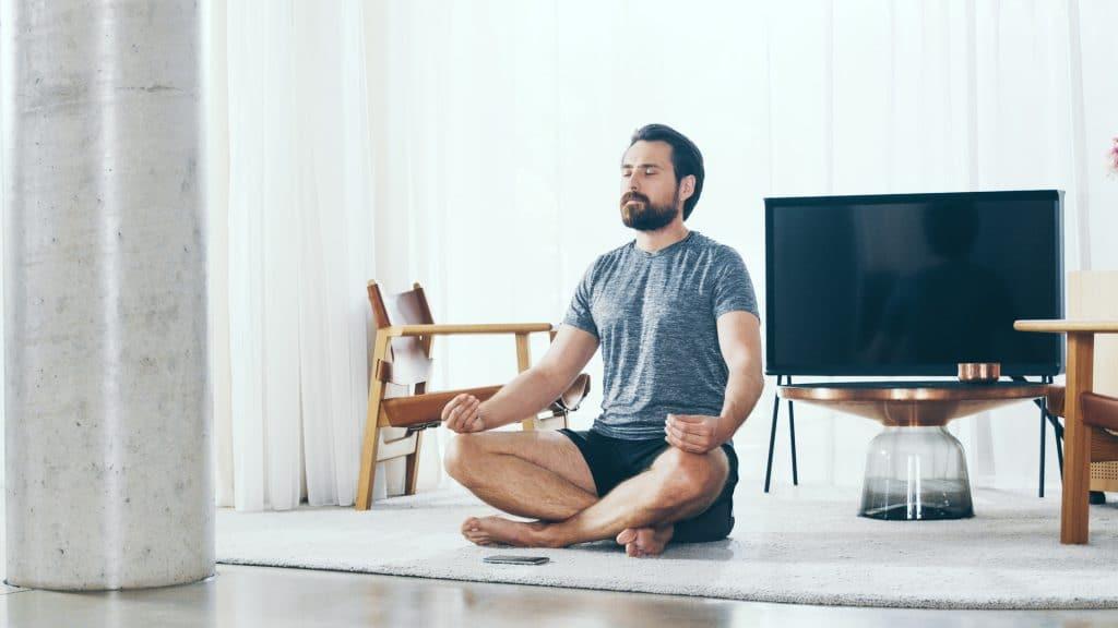 Ein Mann in Sportklamotten sitzt mit gekreuzten Beinen auf dem Teppich im Wohnzimmer und meditiert, Meditation mit My Blossom App, My Blossom, Imagefilm, Erklärfilm, Teaser, WINGMEN Media