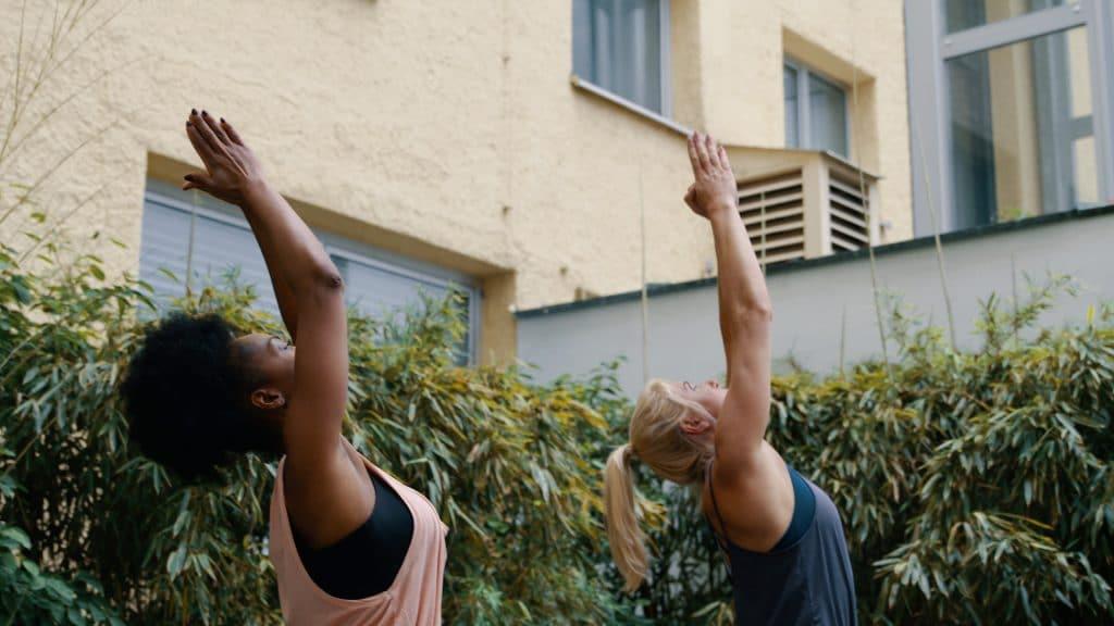Zwei Frauen machen gemeinsam Yoga, Pilates zuhause auf der Terrasse, die Arme sind Richtung Himmel gestreckt, Übungen, Sport, My Blossom, Imagefilm, Erklärfilm, Teaser, WINGMEN Media
