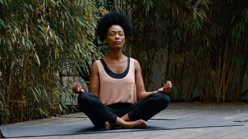 Eine Frau sitzt mit gekreuzten Beinen auf einer Sportmatte, ihre Augen sind geschlossen, Yoga, Meditation, My Blossom, Imagefilm, Erklärfilm, Teaser, WINGMEN Media