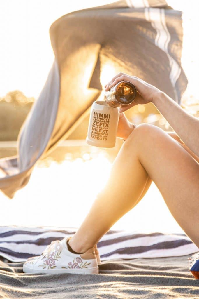 In einen HIMMIHERRGOTT ZEFIX Bierkrug wird Bier eingeschenkt, im Hintergrund wird Handtuch am Chiemsee ausgebreitet, Servus Heimat Laden in Prien am Chiemsee, Servus Heimat GmbH, Produktfotografie, Lifestylefotografie, WINGMEN Media