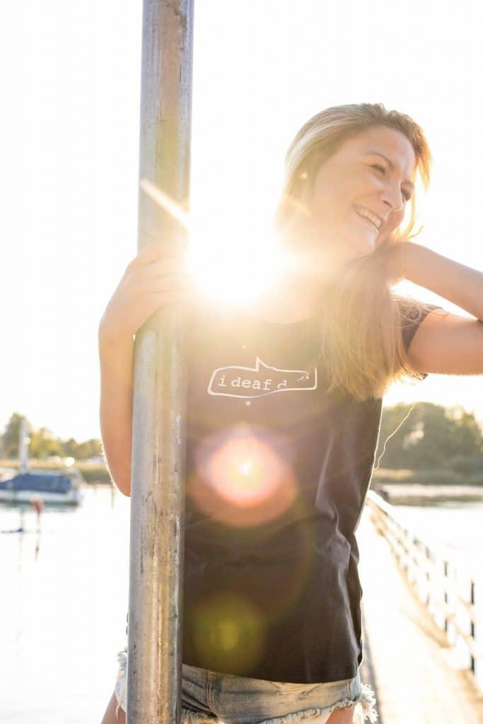 """Eine lachende junge Frau am Chiemsee, sie trägt ein T-Shirt mit dem aufgedruckten Satz """"i deaf des!"""", Sommer am Chiemsee, High-key, Servus Heimat GmbH, Lifestylefotografie, WINGMEN Media"""