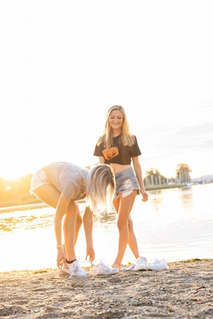 Zwei junge Frauen ziehen Sneakers am Chiemseestrand aus, es ist Sommer, beide sind sommerlich gekleidet, T-Shirt, bayrisch, Servus Heimat GmbH, Lifestylefotografie, Produktfotografie, WINGMEN Media