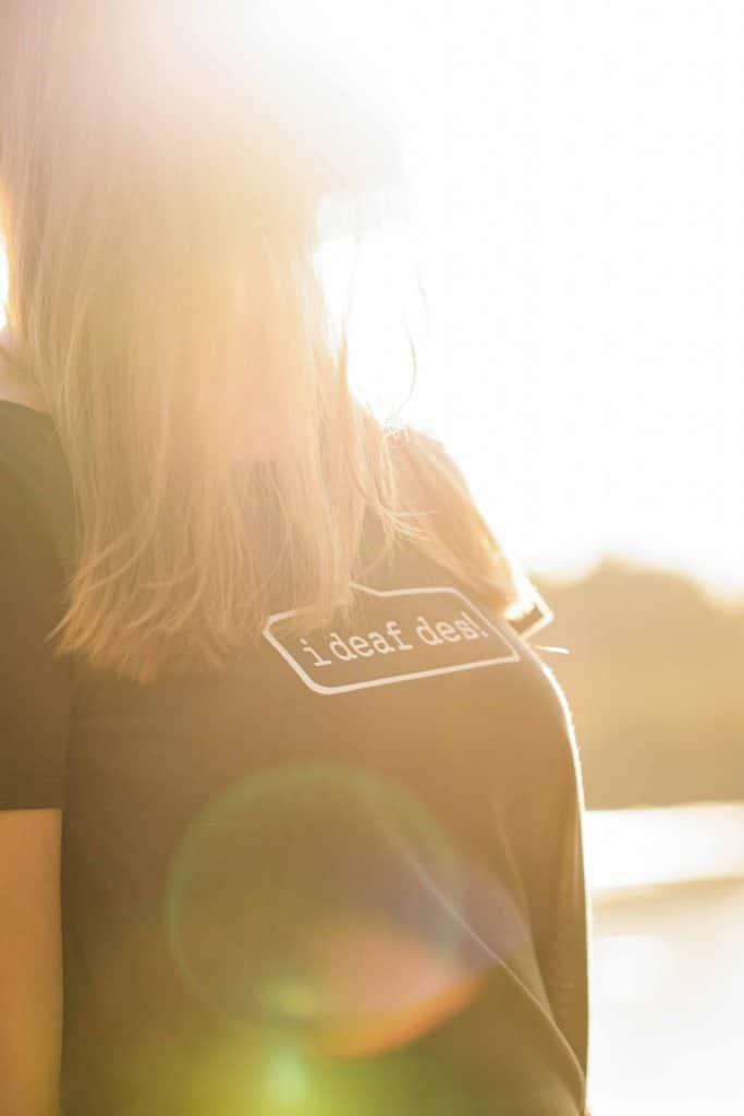 """Ein bayrisches """"i deaf des!"""" T-Shirt im Gegenlicht, eine Frau steht am Chiemseeufer, High-key, Lensflare, Servus Heimat GmbH, Produktfotografie, WINGMEN Media"""