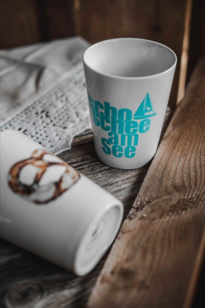 """Zwei weiße Tassen mit """"scho schee am See"""" Aufschrift und Breze als Aufdruck, bayrisch, Tee, Kaffee trinken, Servus Heimat GmbH, Produktfotografie, WINGMEN Media"""