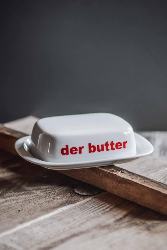 """Eine weiße Butterdose mit roter """"der butter"""" Schrift steht auf einem Holztisch, Geschenk, Souvenir, Servus Heimat GmbH, Produktfotografie, WINGMEN Media"""