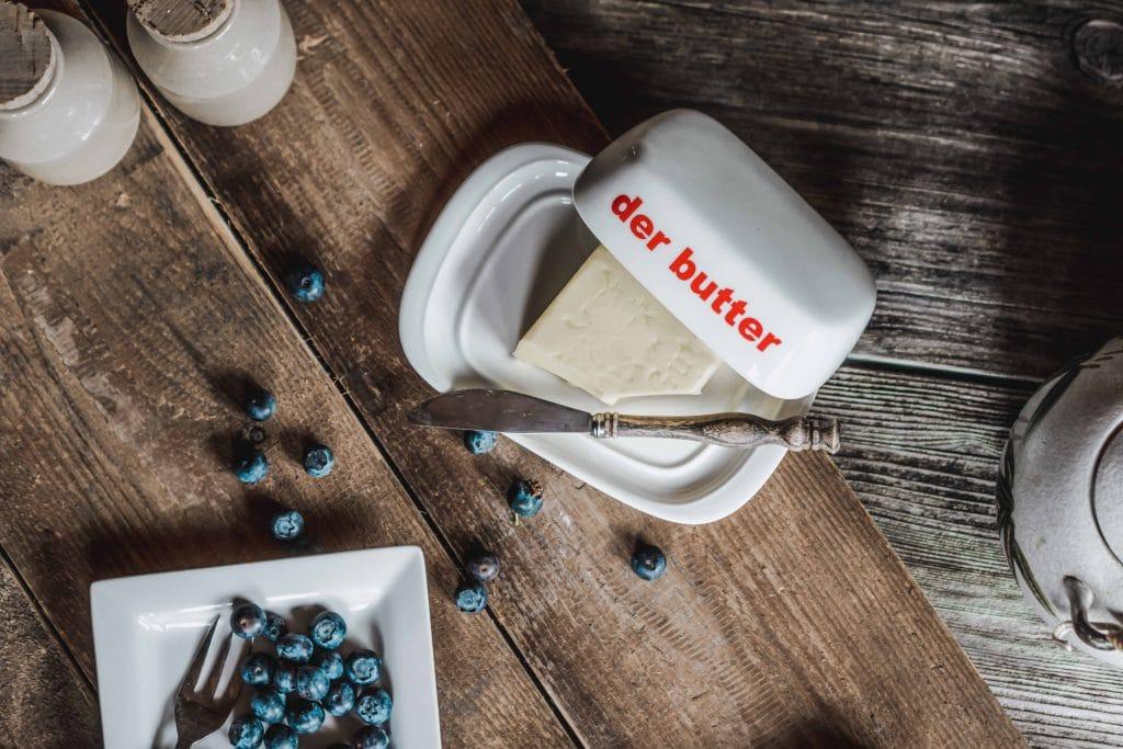 """Topshot einer geöffneten weißen Butterdose mit """"der butter"""" Aufdruck, Butter und ein Buttermesser, daneben steht ein kleiner Teller mit Blaubeeren, auf einem rustikalen Holztisch, Servus Heimat GmbH, Produktfotografie, Food Fotografie, WINGMEN Media"""