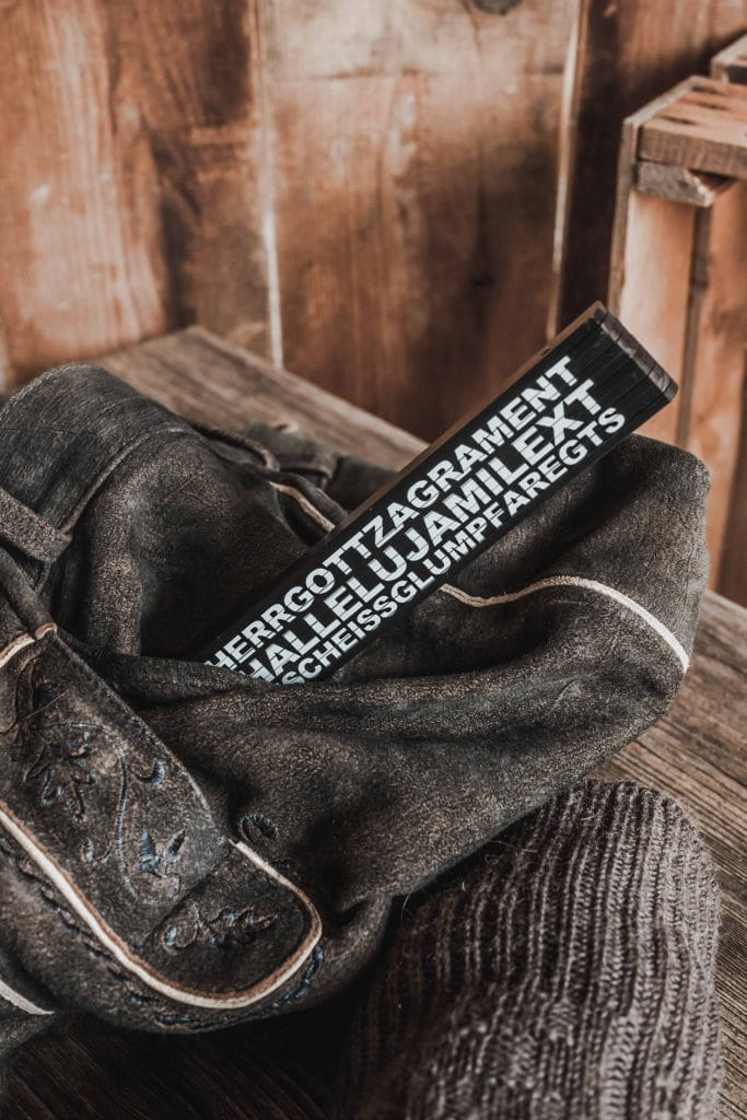Ein Himmiherrgott Zefix Meterstab in einer Hosentasche einer Lederhose, Holztisch, Holzwand, bayrisch, Geschenk, Souvenir, Servus Heimat GmbH, Produktfotografie, WINGMEN Media
