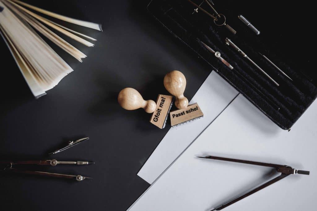 """Ein """"Gfoit ma!"""" und ein """"Passt scho!"""" Stempel aus Holz, auf einem Schreibtisch mit Zirkel, Papier, Geschenke und Souvenirs, Servus Heimat GmbH, Produktfotografie, WINGMEN Media"""