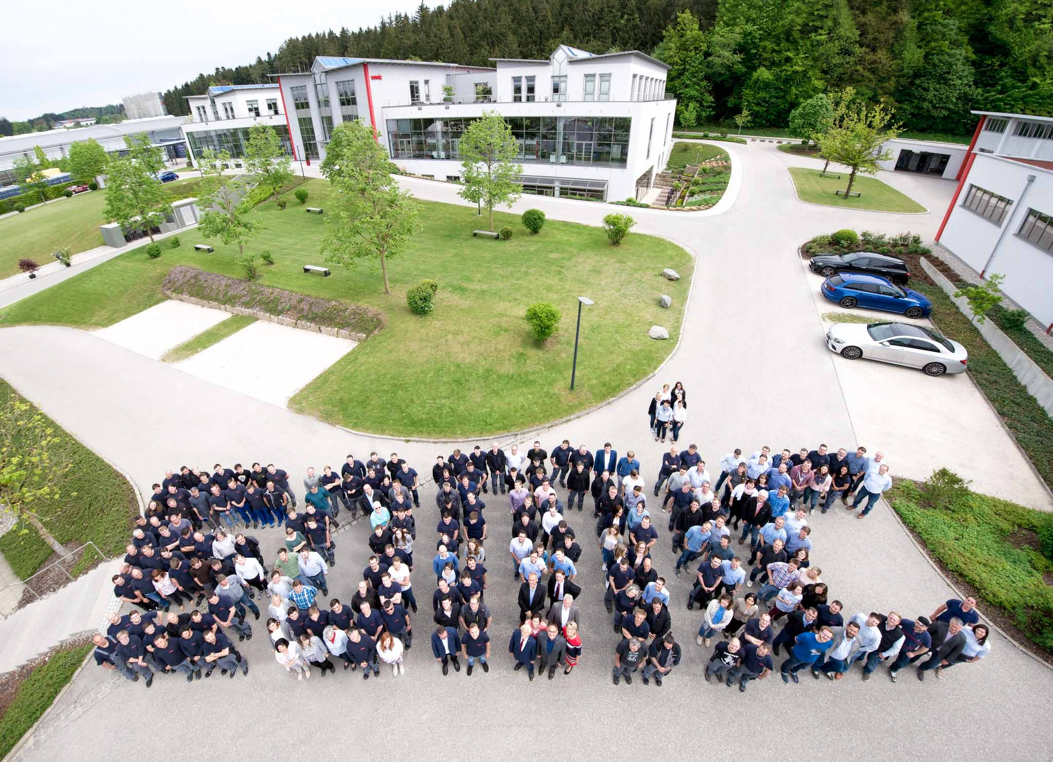 Luftaufnahme von Somic Mitarbeiter aufgestellt als SOMIC Wort, Schrift, vor dem Firmengebäude in Amerang, SOMIC Verpackungsmaschinen GmbH & Co. KG, Mitarbeiterfotografie, Unternehmensfotografie, WINGMEN Media