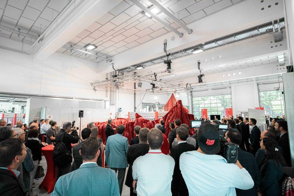 Viele Menschen stehen vor einer neuen Somic Verpackungsmaschine, die hinter einem roten Vorhang enthüllt wird, Event, Tag der offenen Tür, Hausmesse, SOMIC Verpackungsmaschinen GmbH & Co. KG, Unternehmensfotografie, Mitarbeiterfotografie, Eventfotografie, WINGMEN Media