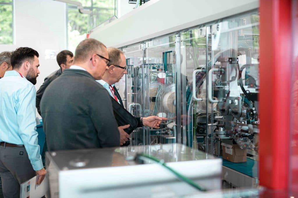 Mitarbeiter sehen sich eine Somic Verpackungsmaschine an, Tag der offenen Tür, Hausmesse, SOMIC Verpackungsmaschinen GmbH & Co. KG, Mitarbeiterfotografie, Unternehmensfotografie, WINGMEN Media