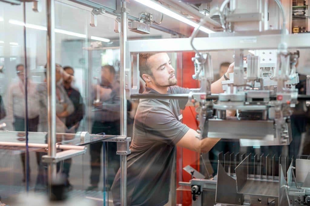 Ein Mitarbeiter bedient, arbeitet an Somic Verpackungsmaschine, Menschen stehen im Hintergrund, Tag der offenen Tür, Hausmesse, Tiefenschärfe, SOMIC Verpackungsmaschinen GmbH & Co. KG, Mitarbeiterfotografie, Unternehmensfotografie, WINGMEN Media