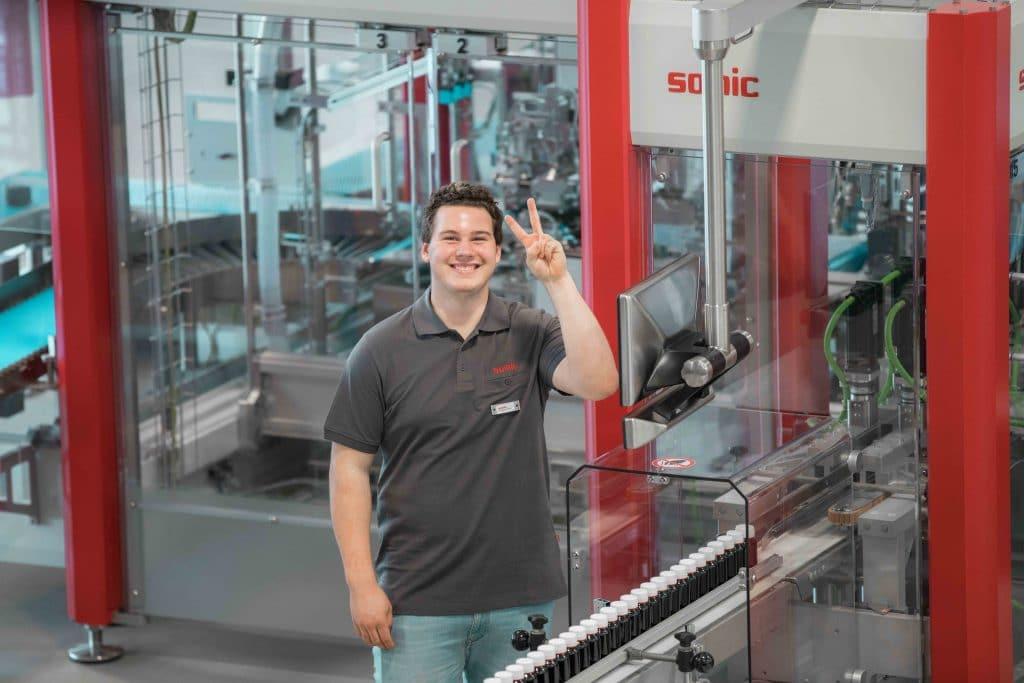 Ein Auszubildender junger Mann neben einer Somic Verpackungsmaschine, lacht und zeigt Peace Zeichen, Hausmesse, Tag der offenen Tür, SOMIC Verpackungsmaschinen GmbH & Co. KG, Mitarbeiterfotografie, WINGMEN Media