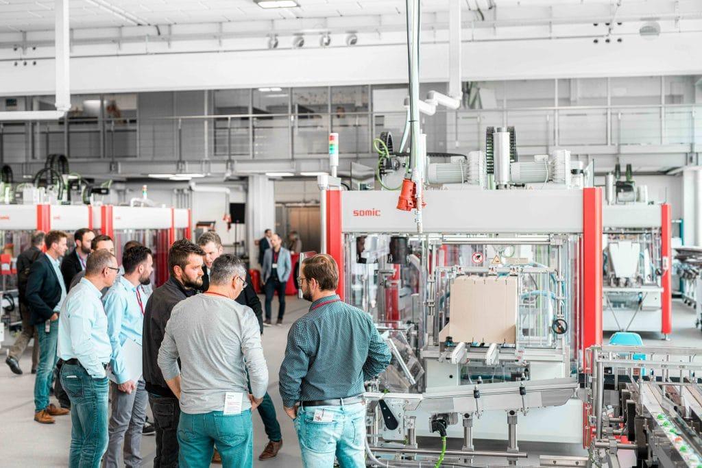 Männer stehen neben einer Verpackungsmaschine von Somic und unterhalten sich, Tag der offenen Tür, Hausmesse, Besichtigung, Maschine, SOMIC Verpackungsmaschinen GmbH & Co. KG, Mitarbeiterfotografie, Unternehmensfotografie, Eventfotografie, WINGMEN Media