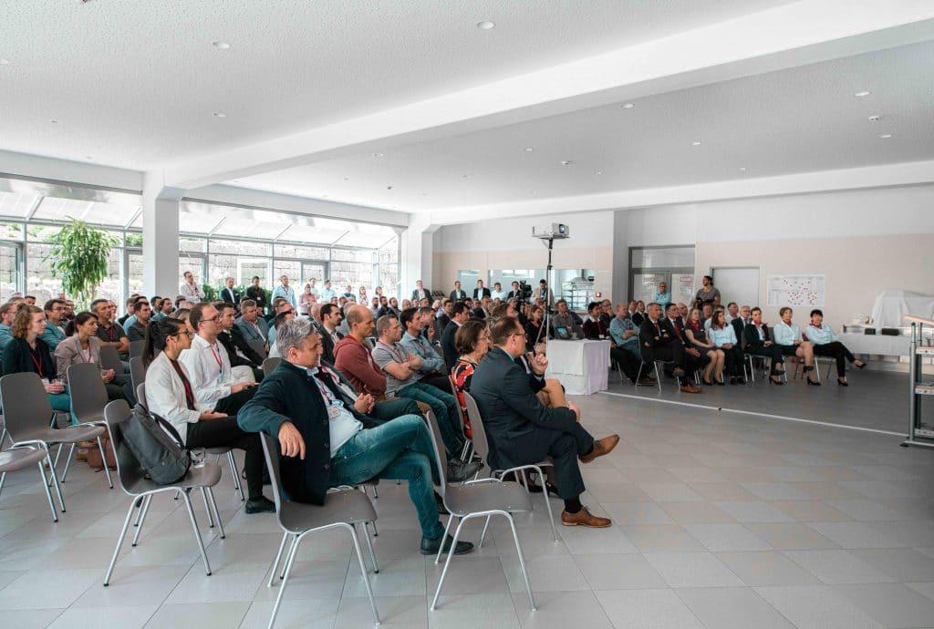 Viele Menschen sitzen in einem Raum und hören bei einem Vortrag zu, Tag der offenen Tür, Hausmesse, SOMIC Verpackungsmaschinen GmbH & Co. KG, Mitarbeiterfotografie, Unternehmensfotografie, Eventfotografie, WINGMEN Media