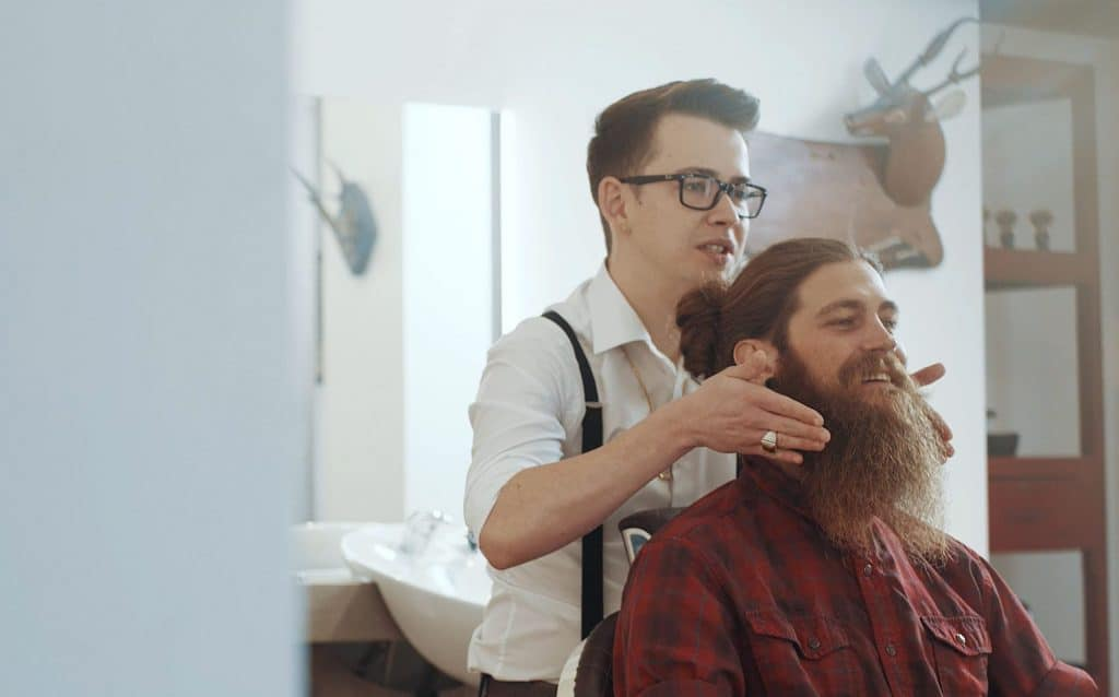 Ein Mann mit Vollbart und Dutt wird in einem Barbeshop beraten, Team Barber, Friseurstuhl, Spiegel, steinzeit für haare, Recruitingfilm, WINGMEN Media