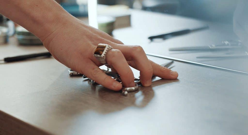 Eine Hand mit Ring greift nach einer Haarschere, Coiffeurschere, ein Spiegel im Hintergrund, Barbershop, steinzeit für haare, Recruitingfilm, WINGMEN Media