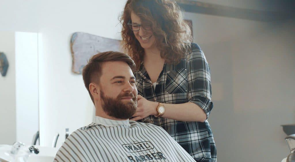 Eine lachende Frau bei der Bartpflege eines Mannes mit Vollbart, Barbershop, Team Barber, steinzeit für haare, Recruitingfilm, WINGMEN Media