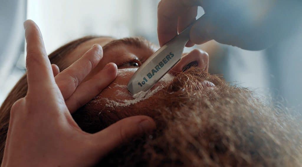 Detailaufnahme von einem Vollbart eines Mannes, der gerade mit einem 101 BARBERS Rasiermesser und Schaum gepflegt wird, Team Barber, Bart, steinzeit für haare, Recruitingfilm, WINGMEN Media
